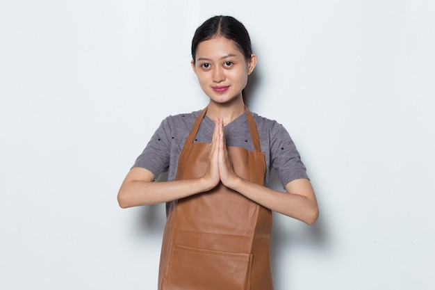 Il barista asiatico della donna indossa il concetto di servizio del caffè del gesto di benvenuto del grembiule