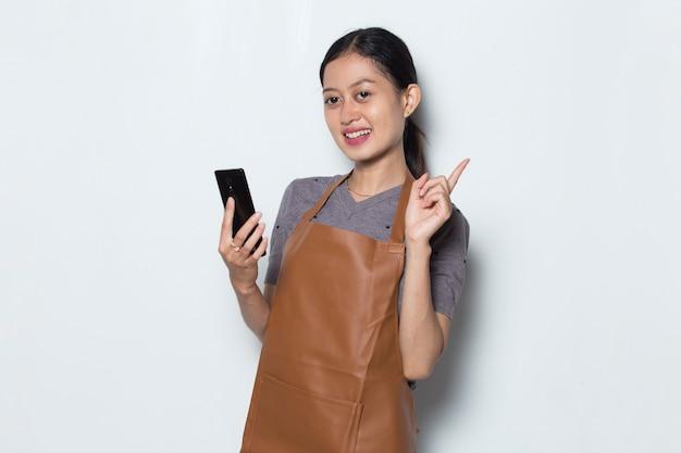 Grembiule di usura del barista della donna asiatica con il concetto di servizio del caffè del telefono cellulare