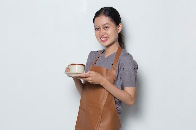 Il barista asiatico della donna indossa il grembiule con il concetto di servizio del caffè della tazza di caffè coffee