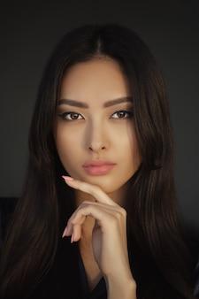 Ritratto asiatico del primo piano del fronte di bellezza della donna. bella ragazza in vestito nero che propone all'interno