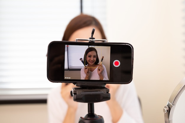 Vlogger o blogger di bellezza donna asiatica in diretta in diretta di clip di tutorial di trucco cosmetico tramite telefono cellulare e condivisione sul canale o sito web di social media, stile di vita di influencer e selfie che prendono immagini
