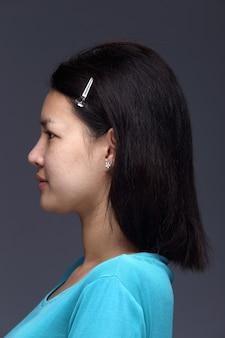 La donna asiatica prima dell'applicazione compone la camicia blu di stile dei capelli neri. nessun ritocco, viso fresco con acne, pelle bella e liscia. sfondo grigio con illuminazione da studio, vista posteriore sul retro