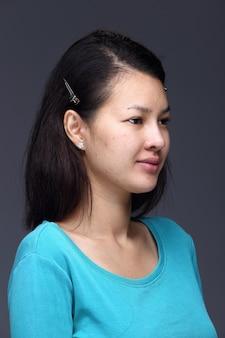 La donna asiatica prima dell'applicazione compone la camicia blu di stile dei capelli neri. nessun ritocco, viso fresco con acne, pelle bella e liscia. sfondo grigio di illuminazione dello studio