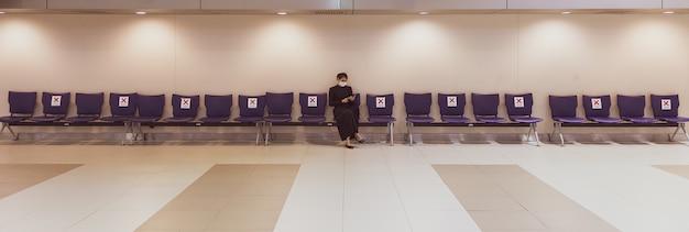 Donna asiatica in un abito nero che indossa la maschera igienica protettiva seduto da solo sulle sedie a schiera e utilizzando uno smartphone.