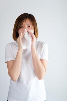 Donna asiatica che soffia il naso