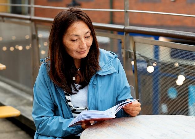 Donna asiatica in un cappotto blu seduto al bar in strada e leggendo un libro