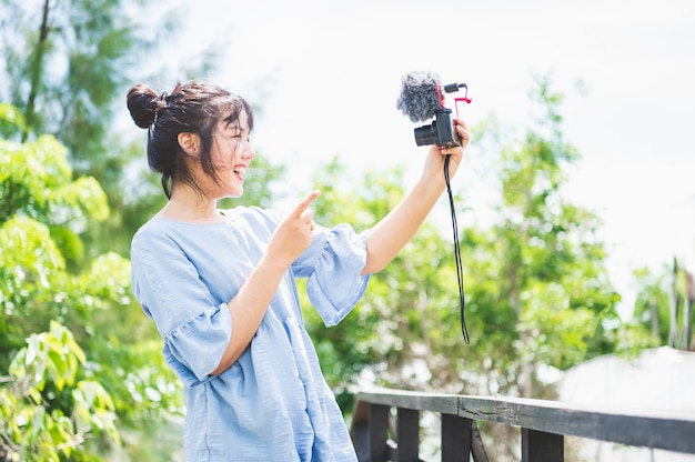 Donna asiatica in abito blu in un parco pubblico che trasporta fotocamera digitale mirrorless e scatta foto e vlog di buon umore. lo stile di vita delle persone e il concetto di svago. viaggio all'aperto e tema della natura.