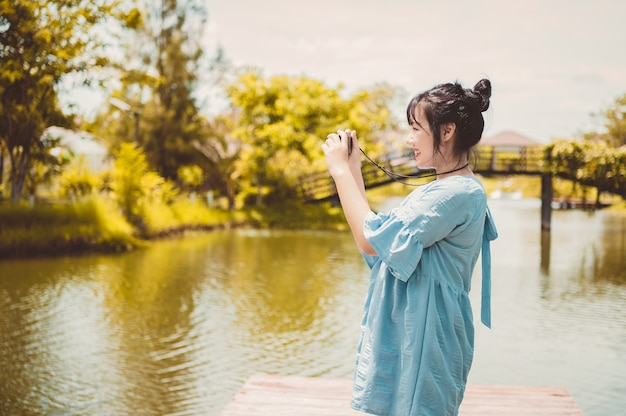 Donna asiatica in abito blu in un parco pubblico che trasporta fotocamera digitale mirrorless e scatta foto senza maschera facciale di buon umore. lo stile di vita delle persone e il concetto di svago. viaggio all'aperto e tema della natura.