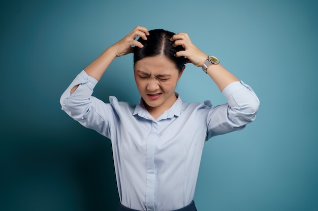 Donna asiatica annoiata e infastidita, grattandosi la testa, isolata sull'azzurro.