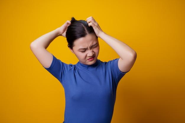 Donna asiatica annoiata e infastidita, grattandosi la testa, sul giallo.