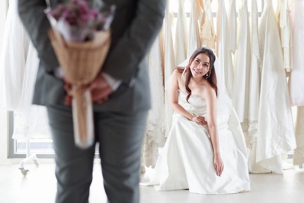 Donna asiatica in un abito da sposa sposo sorridente. lo sposo che indossa un abito grigio tiene in mano un mazzo di fiori viola per sorprendere la sposa che siede nel camerino. il giorno migliore del matrimonio di concetto.