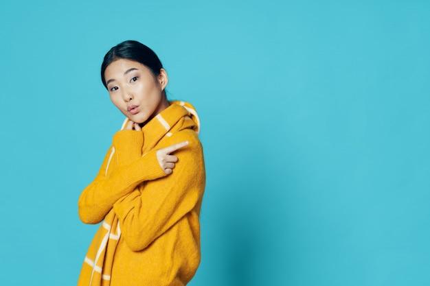 Donna asiatica sul fondo luminoso di colore che posa modello