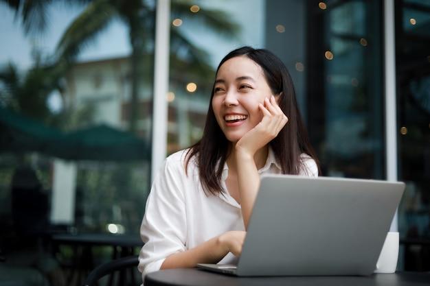 Donna asiatica ad un caffè che lavora ad un computer portatile