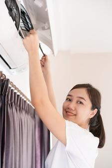 Donna asiatica che cambia un filtro del condizionatore d'aria sporco e polveroso in camera da letto. donna che rimuove un filtro dell'aria sporco all'interno del condizionatore d'aria.