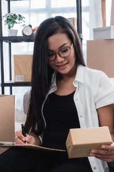 Donna asiatica che controlla i pacchetti di spedizione