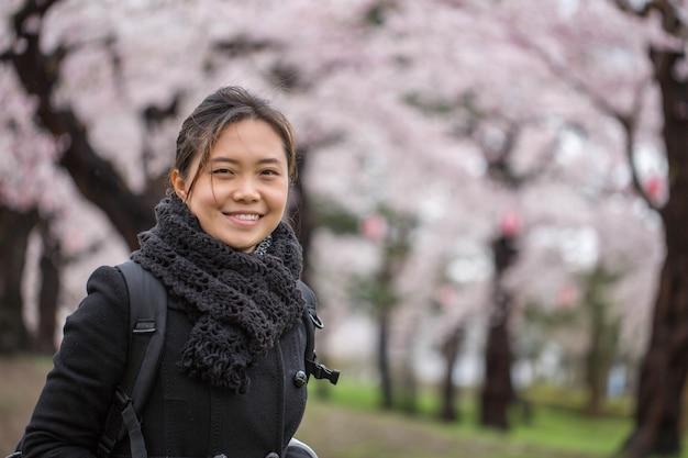 Donna asiatica nel giardino di fiori di ciliegio a hokkaido in giappone.