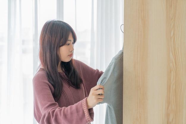 Donna asiatica che sceglie i panni in una stanza