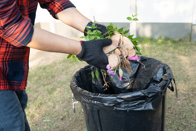 La donna asiatica pulisce e raccoglie i rifiuti secchi delle foglie del cestino nel parco, ricicla, protezione dell'ambiente. team con progetto di riciclo all'esterno.