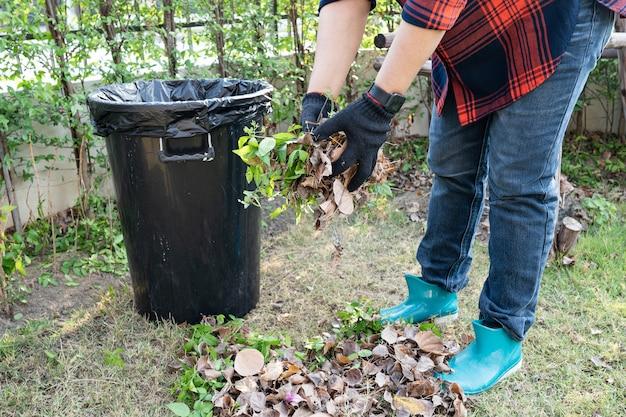 La donna asiatica pulisce e raccoglie rifiuti di foglie secche nel parco, ricicla, protezione dell'ambiente. team con progetto di riciclo all'esterno.