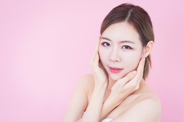 La donna asiatica pulisce la pelle fresca del viso cosmetologia per la cura della pelle chirurgia plastica su sfondo rosa