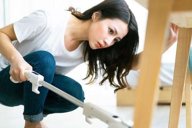 Donna asiatica che pulisce il pavimento con un aspirapolvere