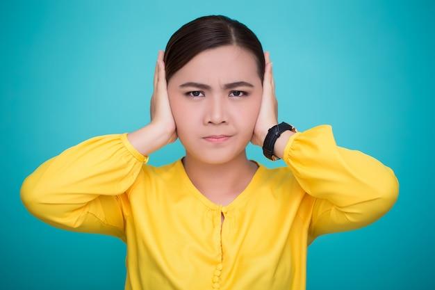 La donna asiatica chiude le sue orecchie