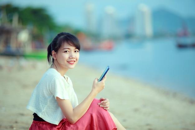 Donna asiatica che collega sul telefono cellulare con la faccia di felicità in spiaggia