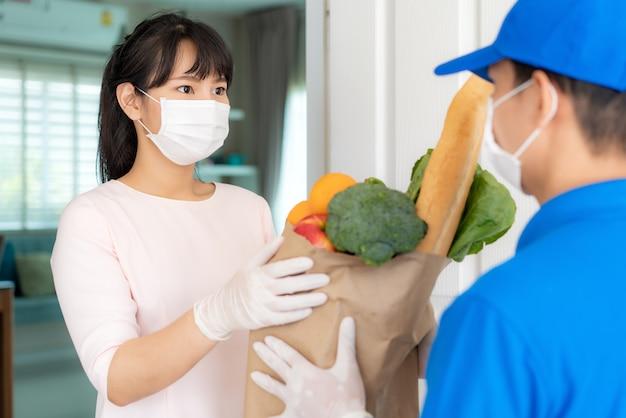 Il costume asiatico della donna che indossa la maschera e il guanto ricevono il sacchetto della spesa di cibo, frutta, verdura dal fattorino davanti alla casa durante il periodo dell'isolamento domestico.