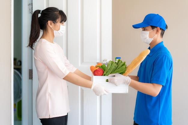 Il costume asiatico della donna che indossa la maschera e il guanto ricevono la scatola della drogheria di cibo, frutta, verdura e bevanda dal fattorino davanti alla casa durante il periodo dell'isolamento domestico.