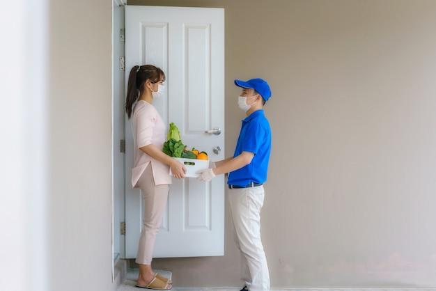 Il cliente della donna asiatica che indossa la maschera e il guanto del viso riceve una scatola della spesa di cibo, frutta, verdura e bevande dall'addetto alle consegne davanti alla casa durante il periodo di isolamento domestico.