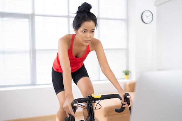 Ciclista donna asiatica. si sta esercitando sull'allenatore