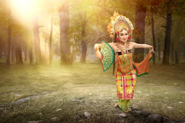 Donna asiatica che balla la danza tradizionale balinese (danza kembang girang) sul campo
