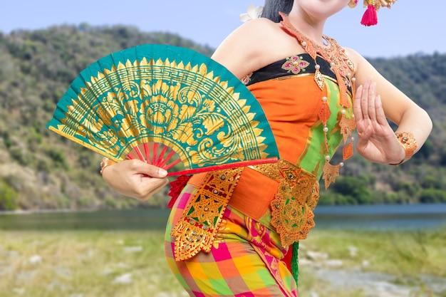 Donna asiatica che balla la danza tradizionale balinese (danza kembang girang) all'aperto