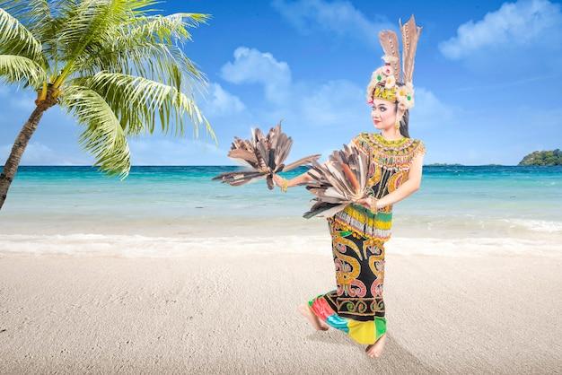 Donna asiatica che balla la danza tradizionale del kalimantan orientale (danza giring-giring) sulla spiaggia