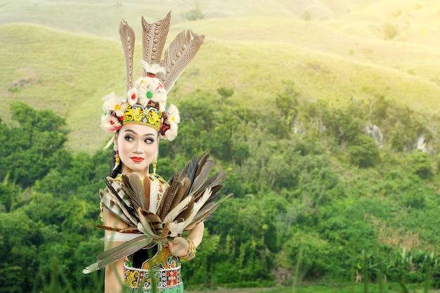 Donna asiatica che balla la danza tradizionale del kalimantan orientale (danza giring-giring) sul campo