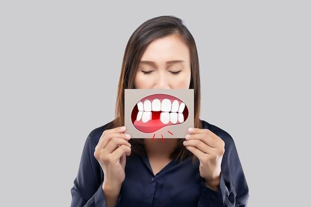 Donna asiatica con la camicia blu scuro che tiene una carta marrone con l'immagine del fumetto del dente rotto della sua bocca contro lo sfondo grigio, dente cariato, il concetto con gengive e denti sanitari
