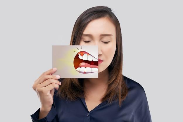Donna asiatica con la camicia blu scuro che tiene una carta con l'immagine del fumetto parodontale e gengivite della sua bocca contro lo sfondo grigio