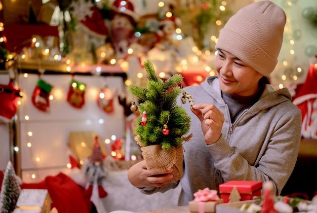 La donna asiatica decora per natale da sola a casa. la famiglia festeggia e felice anno nuovo a casa.