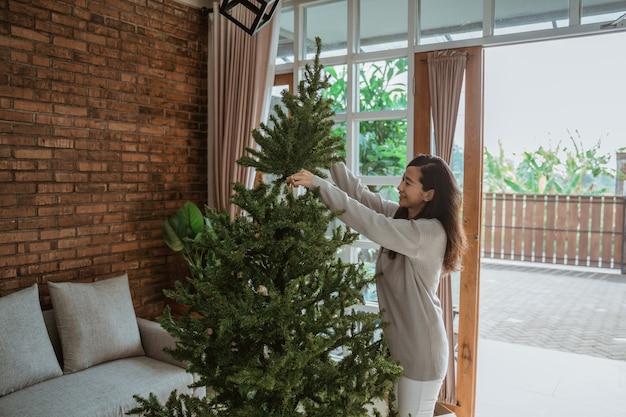 Donna asiatica che decora l'albero di natale
