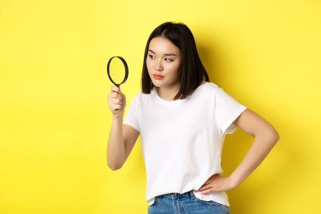 Detective donna asiatica guardando attraverso la lente di ingrandimento con sguardo intrigato, ha trovato indizi, in piedi su sfondo giallo.