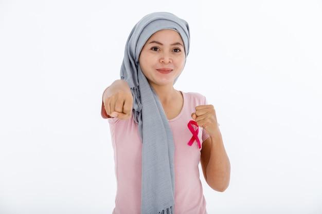 Una donna asiatica malattia malata di cancro mammario che combatte mostrando guantoni da boxe mese di consapevolezza del cancro al seno isolato su sfondo bianco vuoto copia spazio studio, assistenza sanitaria, concetto di medicina