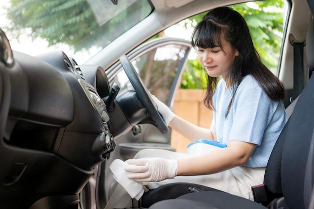 Donna asiatica che disinfetta il cambio dell'automobile dalle salviette eliminabili del disinfettante dalla scatola. prevenire virus e batteri, prevenire covid19, corona virus,