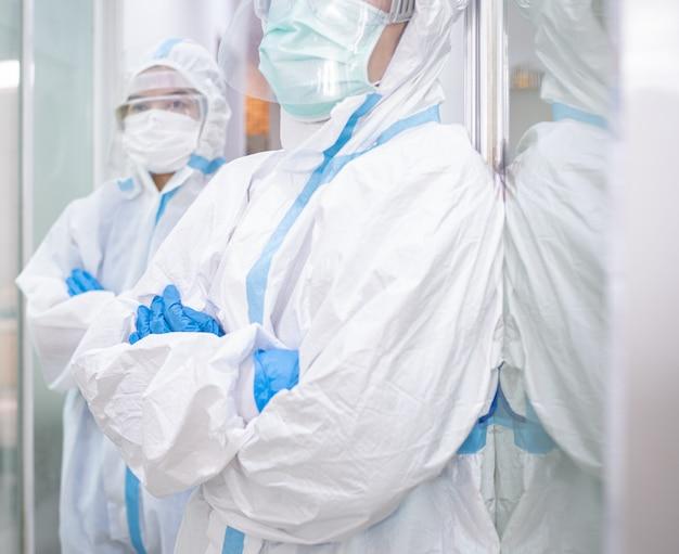 Medico donna asiatica in tuta protettiva personale o dpi indossando maschera e occhiali, in piedi con le braccia conserte combattendo contro lo scoppio covid-19. concetto medico, coronavirus, covid-19 e sanitario.