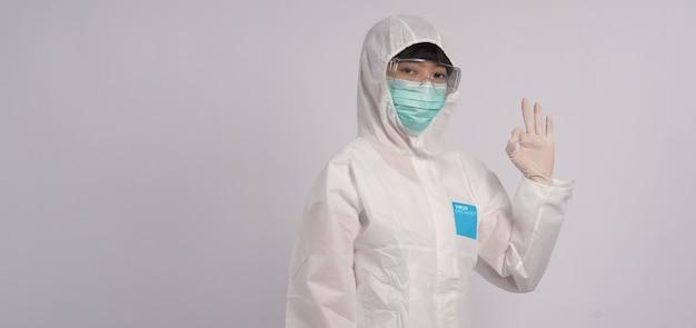 Medico donna asiatica in tuta dpi con cappuccio e indossa maschera medica e guanti per la migliore protezione