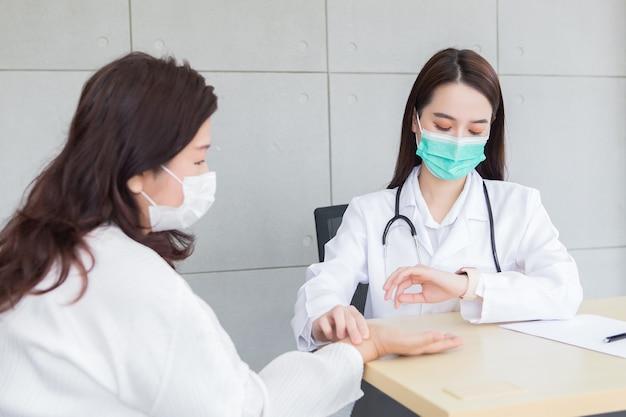 La dottoressa asiatica prende il polso di una paziente mentre guarda l'orologio