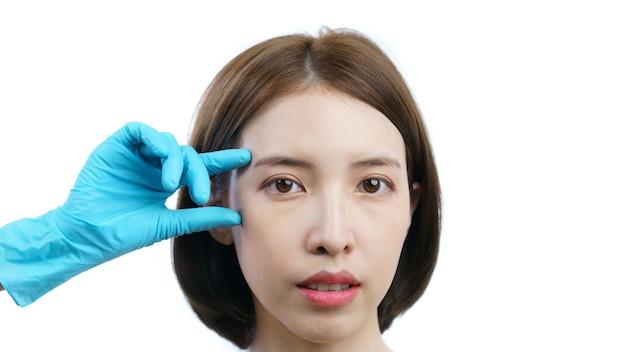 Donna asiatica e medico toccando controllare l'occhio prima di un intervento di chirurgia plastica con pelle sana isolato su bianco