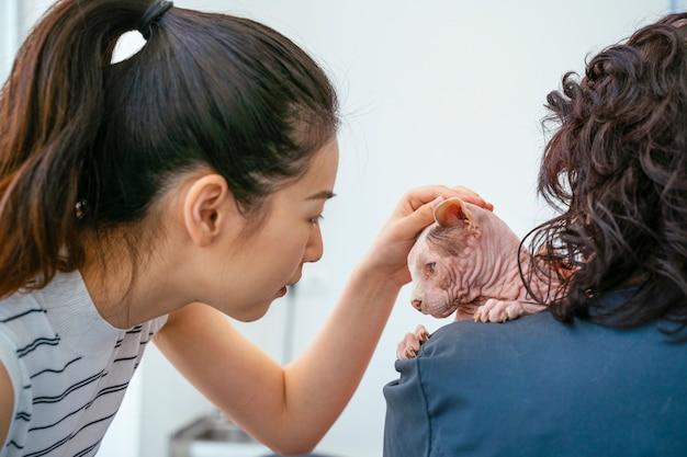 Donna asiatica che fa visita di controllo annuale al veterinario.