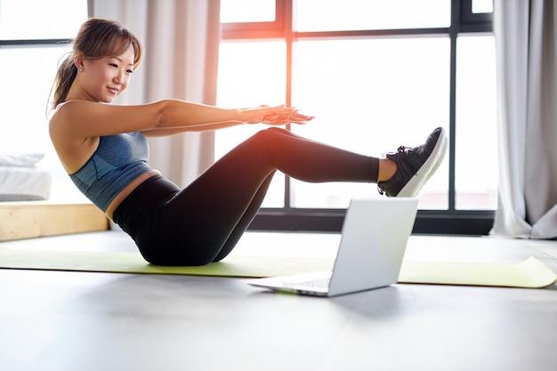 Donna asiatica che fa esercizio addominale sollevamento pelvico sul pavimento, nella stanza luminosa. sport, allenamento, concetto di fitness