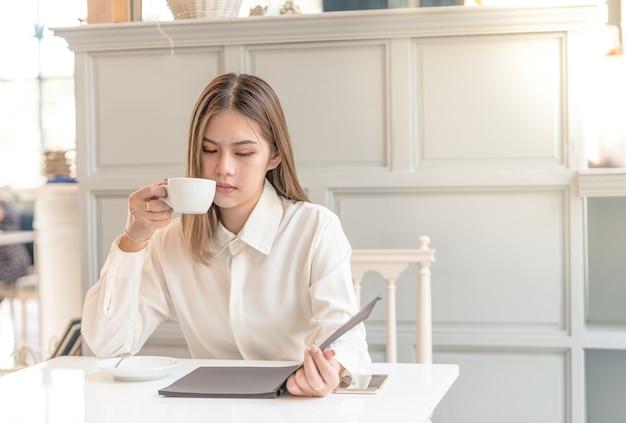 Caffè asiatico della bevanda della donna in caffetteria