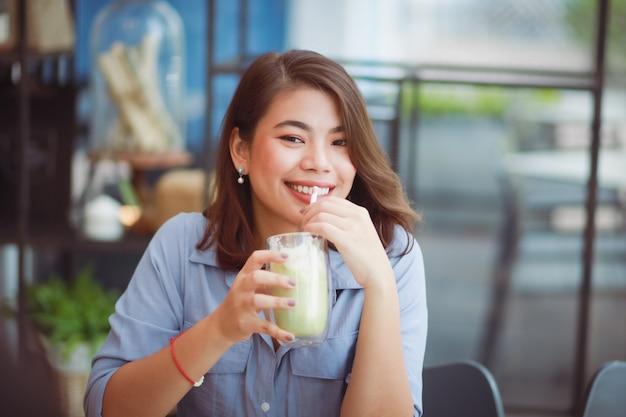 Caffè bevente della donna asiatica nel caffè della caffetteria e per mezzo del telefono cellulare